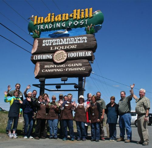 A group of employees from Indian Hill Trading Post celebrates beneath the new sign for the business. ~Talbot photo